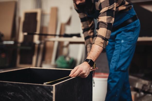 Falegname professionista concentrato che lavora nel suo laboratorio, lavorazione del legno e concetto di artigianato.