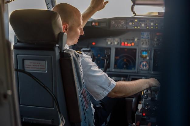 Pilota professionista concentrato seduto in una cabina di aereo, pronto per il decollo. aereo, equipaggio, concetto di occupazione