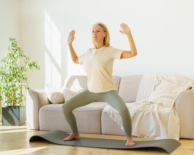 Donna matura in pensione concentrata in abbigliamento sportivo che pratica asana yoga a casa mentre si sta in piedi su mat