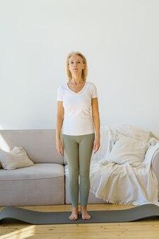 Donna matura in pensione concentrata in piedi mentre fa esercizi di yoga in