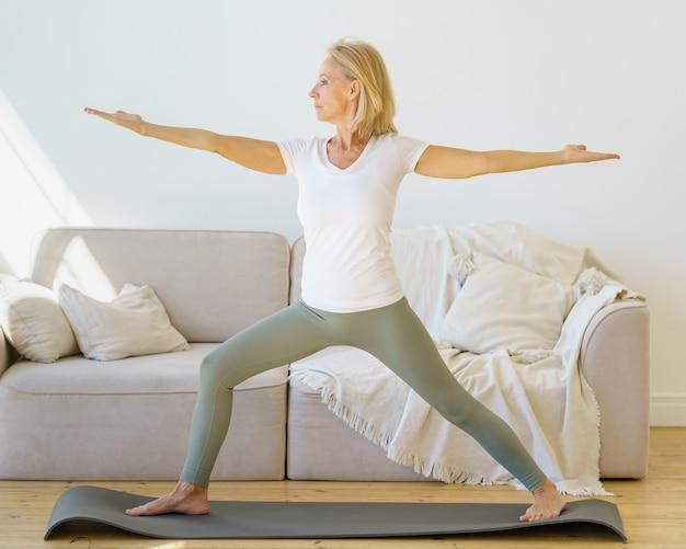 Donne mature in pensione concentrate in abbigliamento sportivo che praticano la posa dello yoga del guerriero a casa