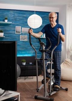 Uomo anziano in pensione focalizzato che lavora alla resistenza delle gambe utilizzando la macchina per biciclette in bicicletta