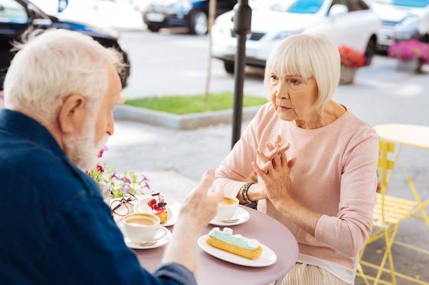 Focalizzato coppia senior parlando e visitando il caffè