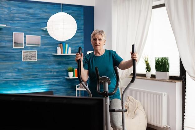 Donna anziana focalizzata che fa allenamento muscolare del corpo guardando video online esercizi in palestra in televisione usando la bicicletta dimagrante a casa nel soggiorno