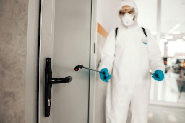 Scatto mirato su uno spruzzatore con sostanze chimiche davanti all'armadietto della porta vita da coronavirus