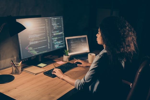 La ragazza afroamericana esperta focalizzata si siede sul computer di lavoro del tavolo della scrivania