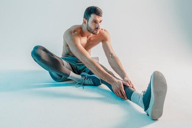 Sportivo concentrato che allunga la gamba prima dell'allenamento. il giovane uomo europeo barbuto indossa l'uniforme sportiva. isolato su sfondo turchese. riprese in studio. copia spazio