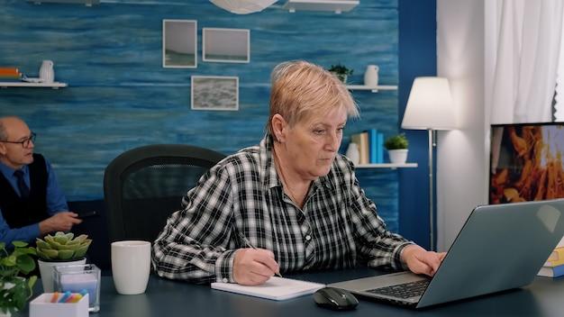 Focalizzato elegante donna anziana matura che lavora a distanza dall'ufficio a distanza di casa sul laptop prendendo appunti a metà...