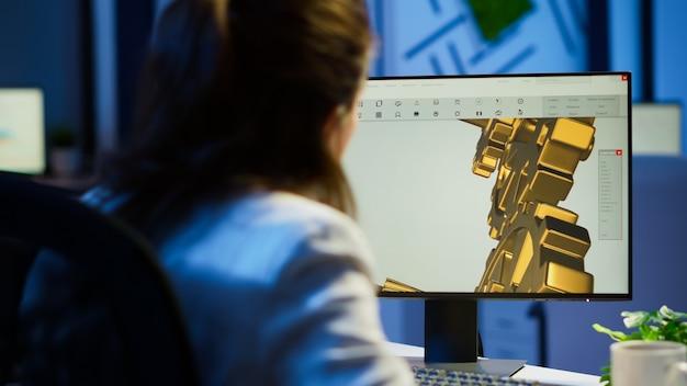 Architetto donna concentrato che lavora al nuovo progetto utilizzando il computer facendo gli straordinari di notte seduto alla scrivania nell'ufficio di avvio. ingegnere industriale femminile che studia su pc che mostra il software cad a mezzanotte