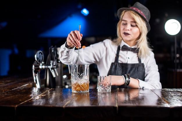Il barista donna concentrato dimostra il processo di preparazione di un cocktail in discoteca