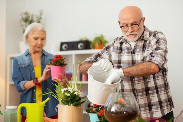 Incentrato sul lavoro. un simpatico uomo anziano che tiene in mano un secchio bianco mentre è impegnato nel suo lavoro