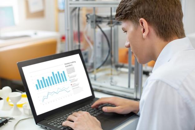 Incentrato sul lavoro. piacevole giovane uomo seduto al tavolo in ufficio e lavorando sul laptop, creando una presentazione