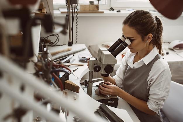 Incentrato sul lavoro. ritratto di giovane gioielliere femminile che esamina il nuovo prodotto di gioielleria attraverso il microscopio in un'officina. concetto di produzione di gioielli. laboratorio di creazione di gioielli. le mani del maestro