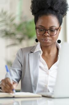 Focalizzato giovane imprenditrice afroamericana o dipendente in giacca sportiva indossare occhiali che lavora al computer portatile in ufficio a casa, prende appunti, guardando il notebook. studente nero ragazza studio. formazione a distanza in linea.