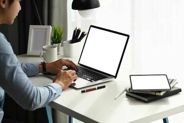 Focalizzato giovane uomo d'affari che lavora con il computer portatile e lavora online in ufficio a casa.