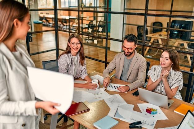 Focalizzato giovane donna d'affari caucasica che mostra grafico su carta a un gruppo di colleghi seduti a tavola con i laptop in ufficio moderno.