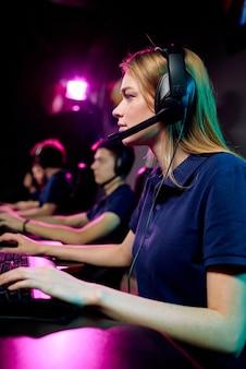 Concentrato giovane giocatore di computer femminile in auricolare a mani libere con microfono utilizzando la tastiera durante il gioco online nel club di e-sport