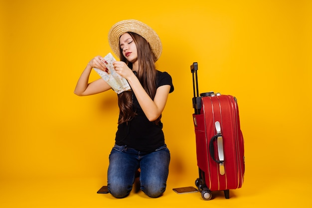 La ragazza concentrata va in vacanza, con una valigia