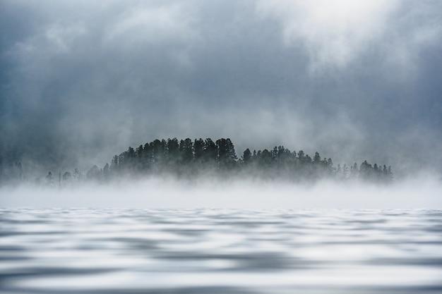 Foresta coperta di nebbia sulla riva di un lago di montagna nel distretto di ulagansky della repubblica di altai, russia