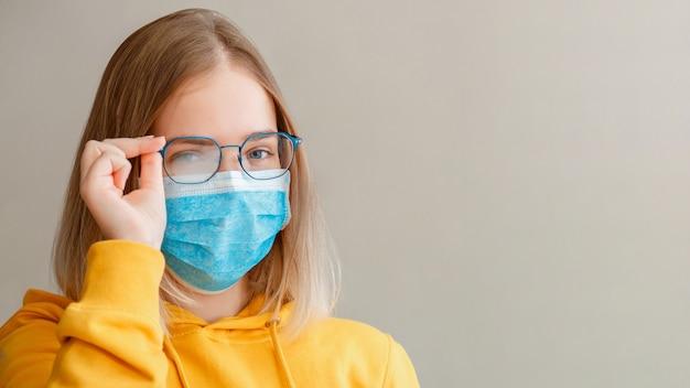 Occhiali nebbiosi che indossano su giovane donna nuovo normale banner web lungo con spazio copia ragazza adolescente in maschera protettiva medica blu e salviette per occhiali occhiali offuscati appannati appannati