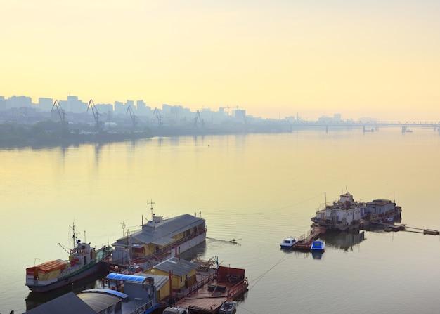 Una mattinata nebbiosa sul fiume ob a novosibirsk ormeggi e navi sulla superficie calma dell'acqua
