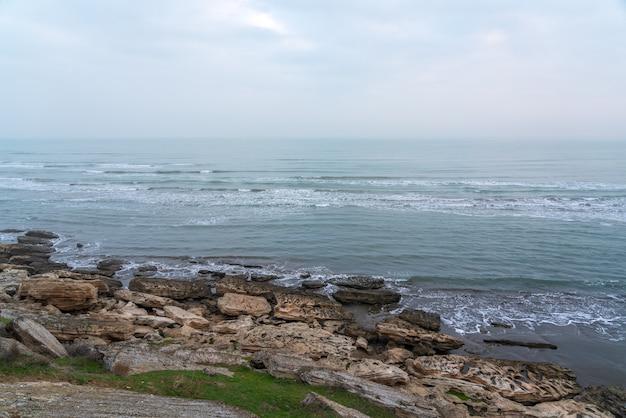 Mattinata nebbiosa sulla costa rocciosa del mare