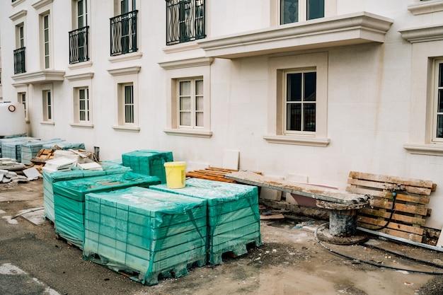 Blocchi di costruzione piegati ricoperti di tela cerata contro la superficie di una casa in costruzione