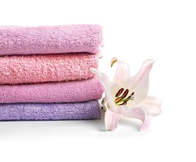 Asciugamani di spugna puliti piegati e bellissimo fiore isolato