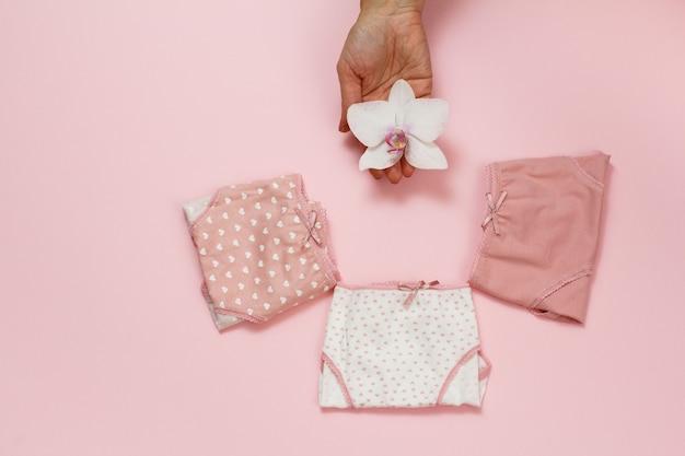 Mutandine di cotone piegate di diverso colore e mano femminile con bocciolo di orchidea su sfondo rosa. completo intimo donna. vista dall'alto.