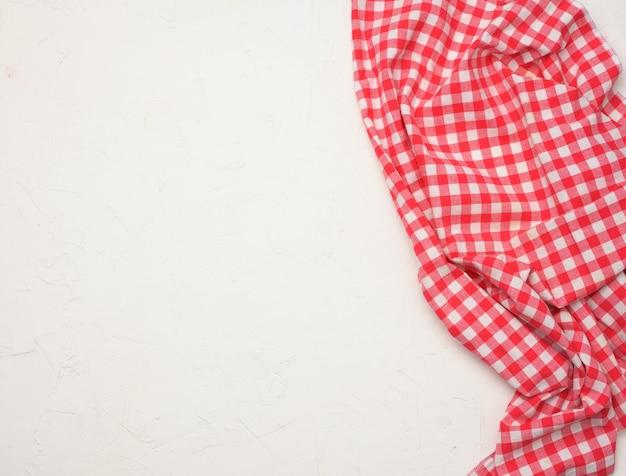 Tovagliolo a quadretti bianco rosso di cotone piegato su un fondo bianco