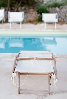 Sedie a sdraio piegate vicino a una piscina in un giardino al tramonto