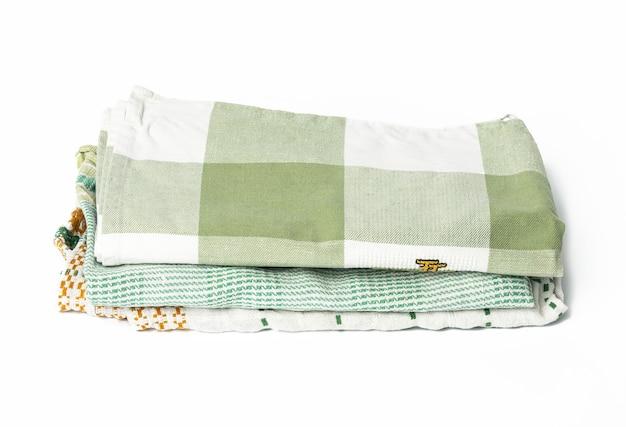 Asciugamano di lino verde piegato su sfondo bianco, vista dall'alto