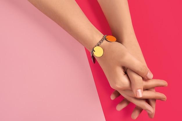 Mani giunte di una giovane donna sconosciuta in un braccialetto di argento lucido o platino