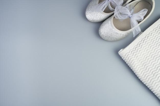 Giacca e scarpe per bambini piegate su fondo grigio-blu.