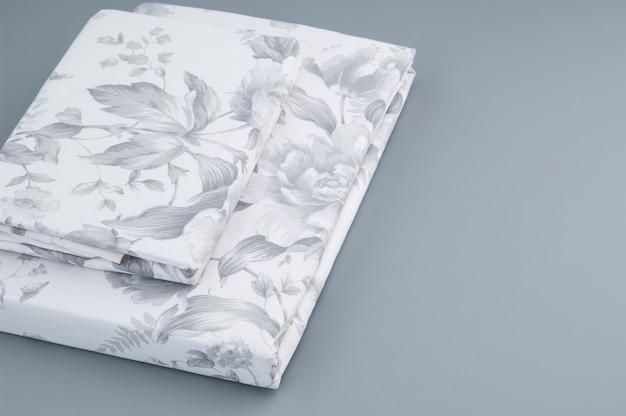 Nuova biancheria da letto piegata con motivi su sfondo grigio, vista dall'alto