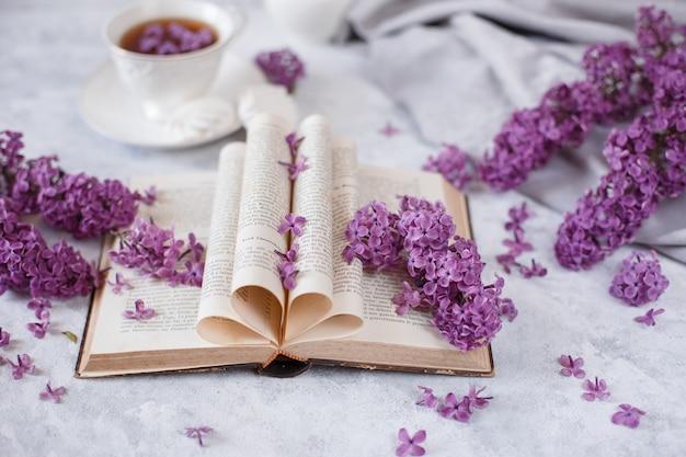 Pagine piegate di un vecchio libro francese con rami di lillà in fiore e petali di fiori