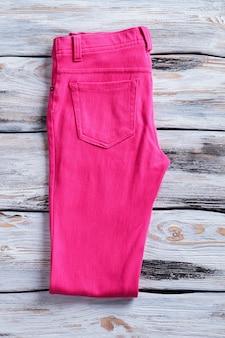 Pantaloni piegati di colore rosa. pantaloni su fondo di legno bianco. pantaloni da donna nuovi di zecca. elegante e colorato.