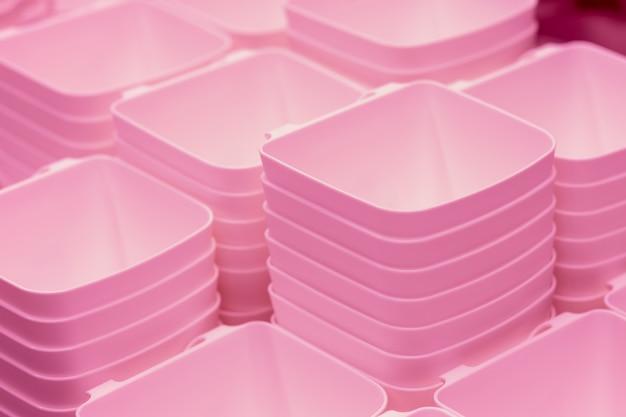 Contenitori di plastica trasparente rosa piegati. ciotole di plastica. contenitori di alimenti in plastica, cestini sullo scaffale del negozio