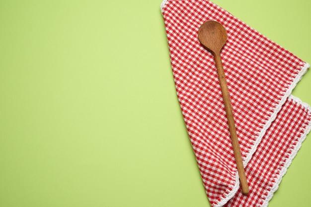 Tovagliolo rosso piegato e cucchiaio di legno