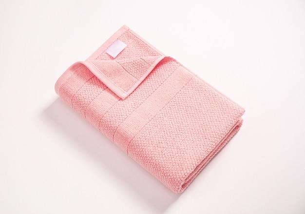 Asciugamano di spugna rosa molle piegato con l'etichetta vuota bianca contro fondo bianco