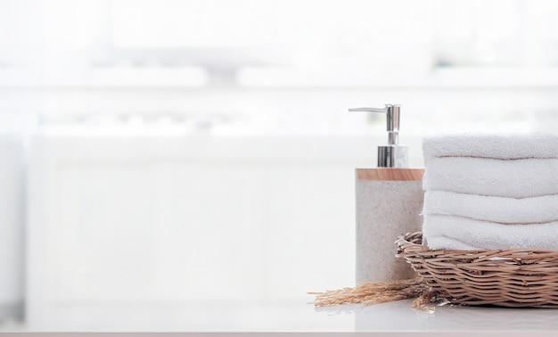 Asciugamano di spugna morbido piegato nel cestino e bottiglia di sapone sul tavolo bianco in bagno sulla luce
