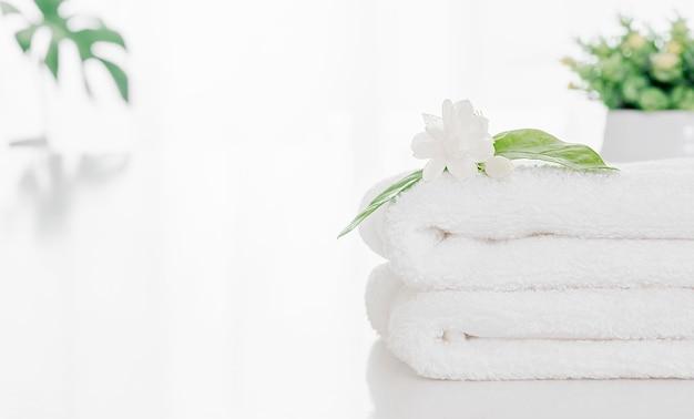Asciugamano in morbida spugna piegato e fiore sul tavolo bianco