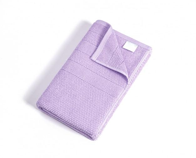 Asciugamano di spugna viola molle piegato con l'etichetta vuota bianca contro fondo bianco