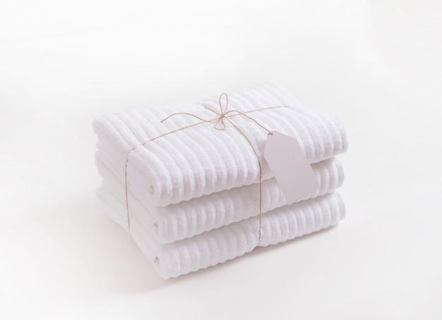 Asciugamani di spugna bianchi piegati e impilati con etichetta vuota