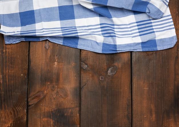 Tovagliolo di cotone blu tessuto piegato su superficie di legno marrone, vista dall'alto, copia dello spazio