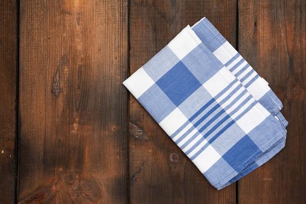Tovagliolo di cotone blu tessile piegato su superficie di legno marrone, vista dall'alto, copia dello spazio