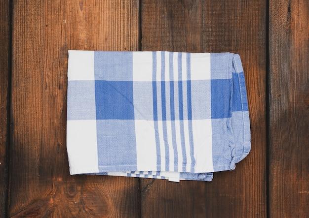 Tovagliolo di cotone blu tessuto piegato su superficie di legno marrone, vista dall'alto