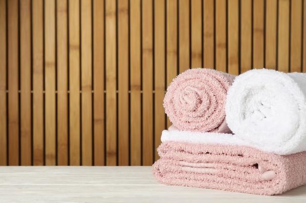 Asciugamani piegati sulla tavola di legno su bambù, spazio per testo