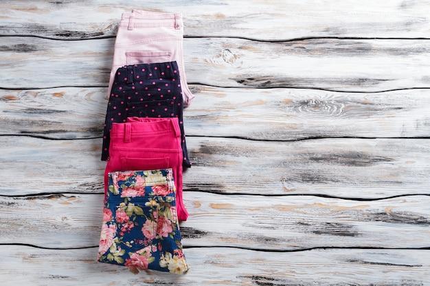 Pantaloni piegati posati vicini. pantaloni blu scuro e floreali. buona selezione di pantaloni da ragazza. solo merce autentica.