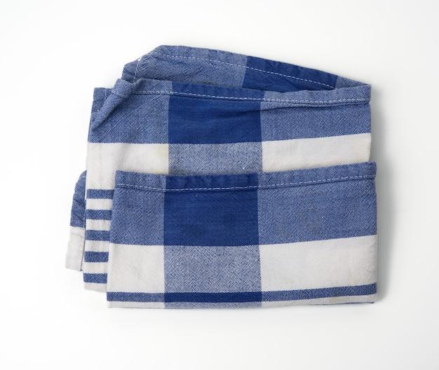 Tessuto di cotone bianco piegato con strisce blu su sfondo bianco, vista dall'alto